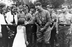 A small girl presents a flowerbouquet to Adolf Hitler in Bad Harzburg. (via axishistory)