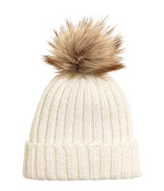 Natural white. Ribbed hat in a soft wool blend with a faux fur pompom at top.