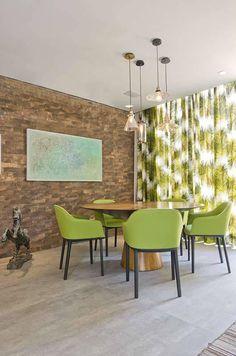 Sala de jantar com parede em tijolo, cortinas estampadas verde, teto branco, luminárias pendentes, mesa redonda, decoração diversa, cadeiras verdes e piso claro.