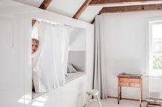 Das Gästezimmer im Obergeschoss der Welle8 Fotolocation hat eine vollverglaste Trennwand zum Wohnzimmer, Verdunklungsvorhänge, eine durchgehende Schrankwand mit integriertem Alkoven, einen gekalkten Kiefernboden, sandgestrahlte Balken, Veluxfenster mit Verdunklungplissee (Drehpunkt oben) im Alkoven nach Osten zur Elbe, Sprossenfenster nach Süden mit Blick durch die Birnenbäume. www.welle8.com #Gaestezimmer #WeißerVorhang