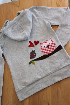 Kuscheliges Kapuzensweatshirt in grau mit einer doppellagigen Kapuze und Känguru-Taschen vorne. Hübsche Knopfleiste, innen weich angeraut. Auf einem Ast sitzen Eule&Spatz mit Herzen. Das Motiv ist...