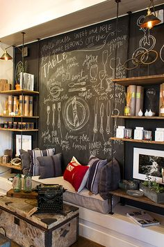 plumbing pipes, wood shelves and a wall painted with chalkboard paint