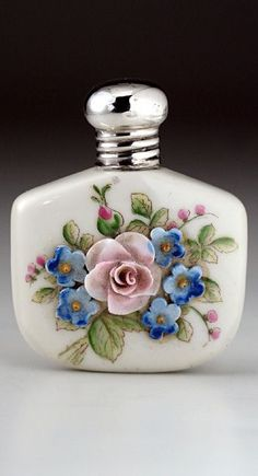 "Cream porcelain scent perfume bottle with a cork lined sterling silver screw cap. The bottle is decorated with a three dimensional porcelain rose, and a further five blue relief flowers on a hand-painted background of leaves and bud sprigs. Silver hallmarked for Birmingham 1920, maker's mark ""DL"" for for Schindler & Co (David Loebl). Height 5.3cm/2.25in. #antique #vintage"