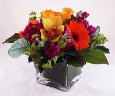 Beautiful summer cube with cymbidium orchid. roses, gerberas, stock, and bluperum.