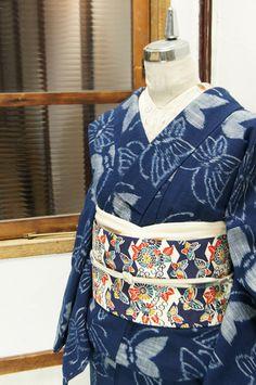 紺色の地に、クレパスで描いたような絣織りのタッチで蝶々模様が織り出された木綿紬の袷着物です。
