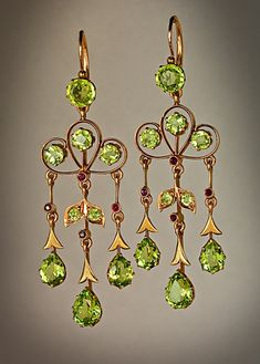 A pair of stylish Art Nouveau chandelier peridot dangle earrings.  Russian, circa 1910  The earrings are handcrafted in rose and green 14K gold and set with round and drop shaped sparkling golden green Uralian peridots.
