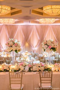 this showstopper wedding reception head table in the four seasons ballroom featured tall lush arrangements of white hydrangea, peach stock, and ivory, peach and blush roses, interspersed along a full flower table runner of white hydrangea, ivory, peach and blush roses, peach stock and lemon leaf.