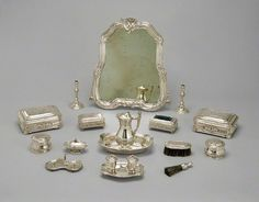 All the little boxes, jars, & brushes that would be set out before the looking glass on a great lady's dressing table. Toilette Service (Service de toilette), Several artists directed by Étienne Pollet, 1738–39. Silver; boar's hair bristles; modern velvet; and modern glass. The Detroit Institute of Arts, Detroit, Michigan. Founders Society Purchase, Elizabeth Parke Firestone Collection of Early French Silver Fund