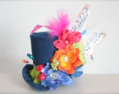 This gorgeous top hat is made with cotton floral and tea pot patterned fabric. For an even more glamorous look this hat has been finished off with ribbon, feathers, lace, rosettes, pearls and rhinestones. This headband is made on an elastic band which is cut to size so please indicate what size you would like in the notes to seller at check out.  Headband sizes are as follows:  Extra Small (Preemies or extra small head -12 ) Small (Newborn to 6 Months -13) Medium (6 to 18 months - 15) Large…