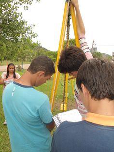alunos realizando medidas do triângulo encontrado, para poder calcular a área do mesmo.