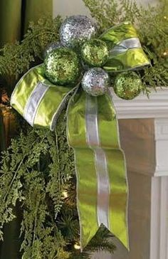 ornaments & ribbon added to garland on the ends of a mantle - simple but beautiful. (love the silver/lime green combo)