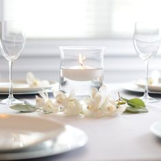 """For a modern-vintage look we love our 6"""" hurricane set. It has a classic hurricane shape with a clear, wide base for great visibility. We've given it a tropical, feminine touch with a wreath of orchids around the base and set it with a table of white and silver plates. #Candles #FloatingCandles #TableSetting #Modern #Vintage #WeddingDecor #White #Silver #Orchids Wedding Decorations, Table Decorations, Floating Candles, Our Love, Vintage Looks, A Table, Orchids, Silver Plate, Table Settings"""