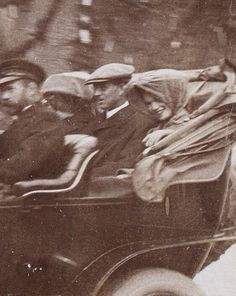 Nicholas II and his first daughter Olga, smiling, in a moving car.