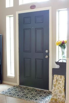 Door color: Sherwin Williams, Iron Ore. (a dark gray color, almost looking black). She used a satin finish (not glossy), SW's All Surface Enamel in latex.