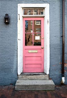 Loving this pink door on a navy brick house! Such a pretty exterior home color combo! Pink and navy home decor, such a cute pink porch!