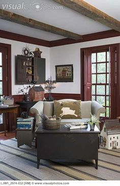 Painted Paneled Walls and Trim, Folkart, a Painted Chest, a Rabbit Pillow on a Settee, a Wall Cupboard, a Tin Lamp, and Ragrugs on the Floor. sitting_areas_sette_sofa_with_rabbit_pillow_cranberry_red_painted_trim_folk_art_accents_stacks_LJW1_2974-032.jpg