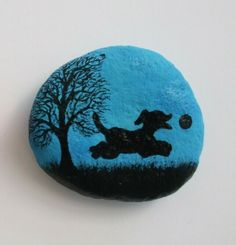 Painted pebble: Dog magnet - Dog and Ball silhouette with tree: Original art painting on stone. The pebble is painted with watercolour (background) and ink and then sprayed with varnish. Approximate stone size: Thank y. Seashell Painting, Pebble Painting, Pebble Art, Stone Painting, Rock Painting, Painted Rocks Craft, Painted Stones, Painted Pebbles, Silhouette Painting