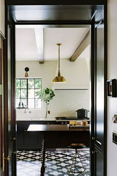 black lower kitchen cabinets, white walls with with hot rolled steel windows - black and white patterned floor