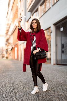 red coat with striped top and skinny pants