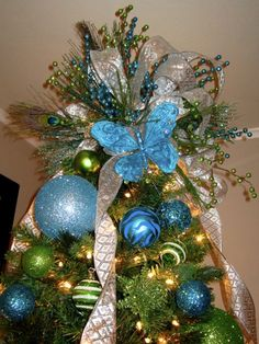 Large peacock-inspired tree topper with lots of blue and green ...