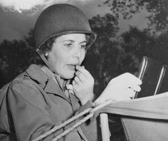 Original caption:The guns of war may be rumbling nearby, but even the perils of battle can't rob the American woman of her right to look her best at all times. Here, on the U.S. Fifth Army Front in Italy, WAC Private Lois Lebert of Lafayette, Louisiana, applies her lipstick outside her tent quarters.