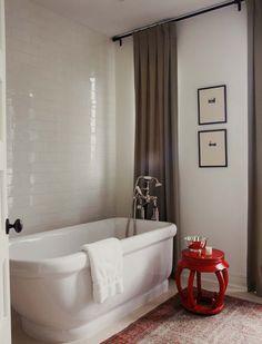 Il pouf di design dona un tocco di colore a un bagno minimal.