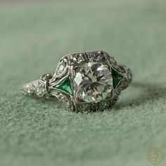 Antique Art Deco Diamond Engagement Ring with Emeralds and diamonds on either side. Estate Diamond Jewelry. Circa 1920. Handmade platinum.