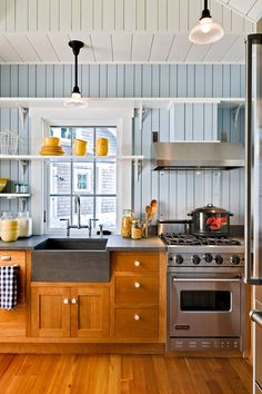 Farmhouse style kitchen with painted bead board and apron sink.