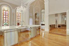 Chrome kitchen appliances with stained glass floor to ceiling windows