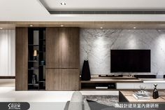 以大理石作為客廳主牆面展現大器穩重的一面,大理石在挑選上主要依自身的喜好選擇紋路與色系,以牆面為主的大理石較不受硬度及吸水率限制,但須留意花紋的拼接效果以及部分雜質的位置是否可以接受,本案件也巧妙地以較深色的木櫃與大理石牆面搭配,使得整體空間內斂沉著卻不顯得過於冷靜。