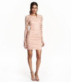En kort, figurnära klänning i genombruten spets med dekorativa bandapplikationer. Klänningen har knäppning i nacken och bar rygg. Lång ärm. Livet och kjolen är fodrad.