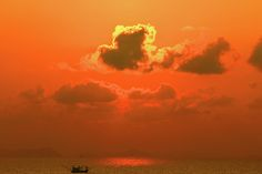 "Sunrise and fishing boat in the South Chine Sea by Gerlya Sunshine. ""The South China Sea is a marginal sea that is part of the Pacific Ocean, encompassing an area of around 3,500,000 square kilometres (1,400,000, sq mi). The area is importance largely results from one-third of the worlds shipping sailing through its waters"". Source: Wikipedia #GerlyaSunshine #seascape #TropicalSunrise #sky #FineArtPhotography #Orange"