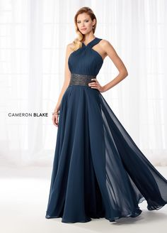This Cameron Blake 218615 dark teal mother of the bride dress features an A-line silhouette with a ruched bodice, inverted halter straps and beaded waistband. This flowy chiffon gown comes with a matching shawl. Young Mother Of The Bride, Mother Of The Bride Dresses Long, Mothers Dresses, Bride Groom Dress, Bride Gowns, Cameron Blake, Cocktail Dresses Online, Womens Dress Suits, Evening Dresses