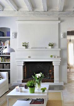 Salon blanc avec cheminée, spacieux et lumineux.