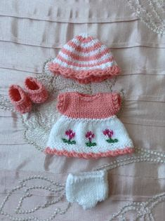 Hand knitted dolls outfit to fit a 5 Berenguer Itty Bitty baby doll/Cupcake doll. Knitted in baby yarn and consisting of a dress, hat, pants and shoes. The skirt of the dress is knitted in white, with three little knitted in flowers across the front in fuschia pink. The bodice is in