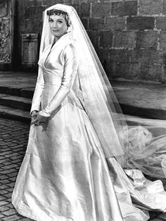 Julie Andrews' wedding gown in THE SOUND OF MUSIC.  The American couturier Main Rousseau Bocher (1890-1976).  This white satin gown is so simple!  No lace or embellishment of any kind.  Long sleeves, pointed at the wrist and an a-line silhouette.  The Amazing thing is the 10-12 foot train and veil!!