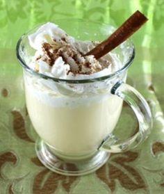Creamy light yellow cocktail in Irish coffee mug with whipped cream, nutmeg and a cinnamon stick