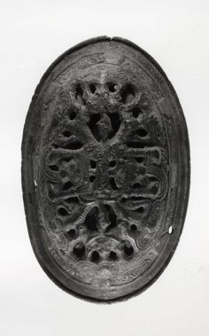Bronze oval brooch: two-piece construction; openwork upper shell decorated in Borre Style animal interlace; lower shell with Jellinge style ribbon interlace animals.  Findspot:  Gotland, Sweden. Date:  9th-10th century CE.  In the British Museum.