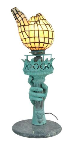 "A patinated cast bronze lamp with circular marble box having a leaded glass shade depicting the arm and torch of the Statue of Liberty.  Piece is in working order. Measures 22"" x 9.5"" and weighs 17 lbs. From the Estate of Blandy Boocock."