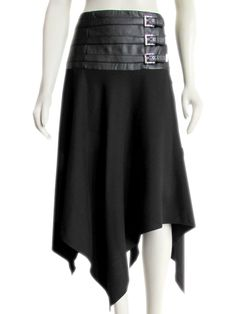 Gorgeous Escada black wool skirt trimmed in vegan /faux leather, and finished with an asymmetrical hem. While certainly sophisticated, this skirt definitely 'tips it hat' to bondage or fetish inspire fashion with the buckled leather trim at the hips. Draped below the hips in  bias cut wool which falls freely to form an eye catching asymmetrical hem. Finished with a hidden side zip and partial lining at the hips.