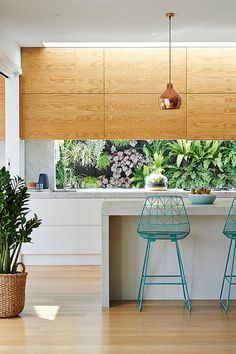 Wood kitchen cabinetry with lush green botanical backsplash