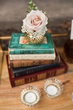 Romantic Marsala New York Wedding Inspiration at the Rushmore Estate - MODwedding. Quicksand rose with rice flower in small cup atop vintage books. Floral by Dancing Tulip Floral Boutique.