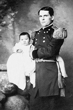Baby girl Zintkala Nuni (Little Lost Bird) survivor of Wounded Knee massacre, found on battle field is being held by Gen. Colby of Nebraska State Troops, 1890.