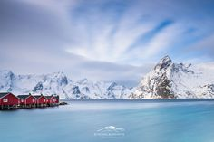 Red on Blue - Red fishing cabins on Hamnoy Harbor in the Lofoten Islands. I took a one-minute exposure to create the smooth water surface and to capture motion in the clouds. The red cottages are in contrast to the cyan hues of the Norwegian Sea, and the white of the snow-capped mountains.
