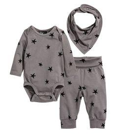 Mattlila/Sterne. CONSCIOUS. Set mit Body, Hose und Mütze aus weichem Bio-Baumwolljersey. Body mit Kreuzverschluss, langen Ärmeln und Druckknöpfen im Schritt