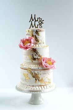 Semi naked wedding cake with gold leaf foil and sugar peonies.