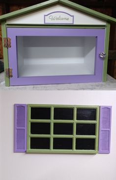 """This whimsical """"Lilacs & Lilies"""" little free library painted Leapfrog Green and Brave Purple with its 3D printed Welcome sign and matching windows with miniature shutters is headed for Menomonie, Wisconsin, where it will be installed in front of its matching cottage. Built by Little Library Builder of Spokane! www.littlelibrarybuilder.com Little Free Libraries, Little Library, Free Library, Menomonie Wisconsin, Lilacs, Shutters, Brave, Whimsical, Miniature"""