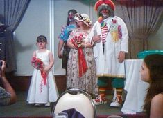 Its not weird enough for the marrying couple to look like that, they made the best man and a very annoyed flower girl wear clown noses!