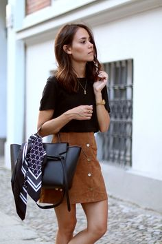 Suede skirt. Black top, handbag.  Gold accessories- Necklace and watch.
