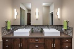 The double vanity in this spa-like master bath has sleek straight lines that gives it a modern contemporary look. The backsplash adds a fun texture with a stone and glass square mosaic.